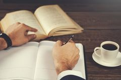 Blocco note della mano dell'uomo con il libro ed il caffè immagine stock