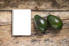 Blocco note di ricetta con l'avocado due su fondo di legno Fotografie Stock Libere da Diritti