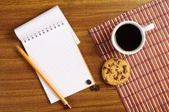 Blocco note e caffè con i biscotti fotografie stock libere da diritti