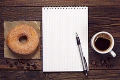 Blocco note e caffè con la ciambella immagine stock libera da diritti