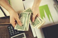 Blocco note e calcolatore della mano della donna con soldi fotografia stock