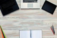 Blocco note e computer portatile sulla tavola di legno Vista da sopra Immagini Stock