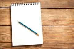 Blocco note e matita su legno Immagine Stock