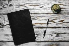 Blocco note e penna su una tavola bianca Fotografie Stock