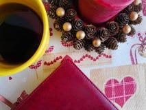 Blocco note e tazza da caff?, caff? al di sotto della candela, blocco note rosso Tazza di caff? bianca sulla tavola e sulle mani  fotografia stock