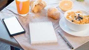 Blocco note e telefono cellulare con lo schermo in bianco vicino alla prima colazione sana fotografia stock libera da diritti