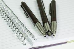Blocco note e tre penne fotografia stock libera da diritti