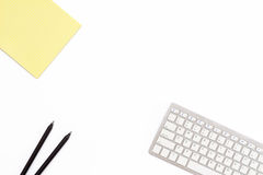 Blocco note giallo, due matita nera e tastiera su un fondo bianco Disposizione piana Vista superiore Immagine Stock