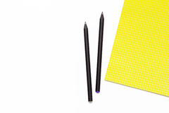 Blocco note giallo e matita nera due su un fondo bianco Concetto minimo di affari del posto di lavoro negli uffici Fotografie Stock Libere da Diritti