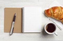 Blocco note, penna, caffè e croissant fotografia stock