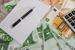 Blocco note, penna e calcolatore su un euro fondo fotografia stock libera da diritti