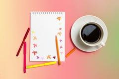 Blocco note, pennarelli colorati, tazza con caffè su fondo giallo pastello Autunno di concetto Immagini Stock Libere da Diritti