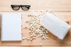 Blocco note per le entrate, i vetri 3d ed il popcorn salato Fotografia Stock