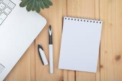 Blocco note pulito, computer portatile, penna, su superficie di legno fotografia stock