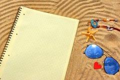 Blocco note a quadretti di giallo, degli occhiali da sole ed oggetti differenti sulla t Immagini Stock