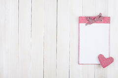 Blocco note rosso del plaid sul recinto bianco Fotografie Stock Libere da Diritti