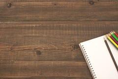 Blocco note a spirale aperto con la pagina in bianco e molte matite di colore Fotografia Stock Libera da Diritti
