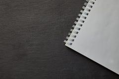 Blocco note a spirale bianco in bianco sulla tavola nera Vista superiore Immagine Stock Libera da Diritti
