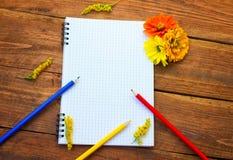 Blocco note a spirale in bianco con le matite ed i fiori immagine stock libera da diritti