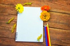 Blocco note a spirale in bianco con le matite ed i fiori immagini stock libere da diritti
