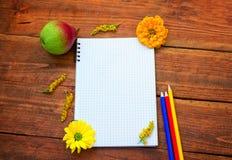 Blocco note a spirale in bianco con le matite, la pera ed i fiori fotografia stock libera da diritti