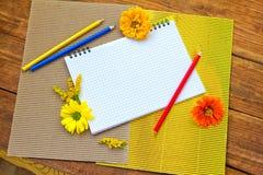 Blocco note a spirale in bianco con le matite variopinte ed i fiori immagine stock libera da diritti