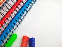 Blocco note a spirale con le penne di indicatori Pila di taccuini variopinti isolati su fondo bianco Colorato - blu, rosso, verde fotografia stock libera da diritti