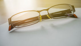 Blocco note a spirale degli occhiali che si trova su un buio Immagine Stock Libera da Diritti