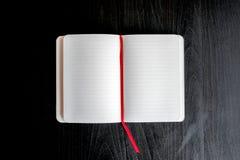 Blocco note su una tavola scura con il segnalibro rosso Fotografie Stock Libere da Diritti
