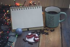 Blocco note, tazza blu, pupazzo di neve del giocattolo dell'albero di Natale sulla tavola immagini stock libere da diritti