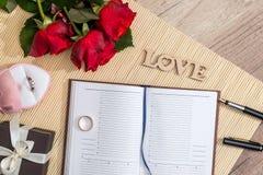 blocco note vuoto con le rose rosse, contenitore di regalo, amore del testo Fotografie Stock