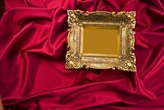 Blocco per grafici del vecchio oro su raso rosso Immagine Stock Libera da Diritti