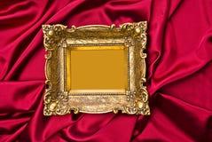 Blocco per grafici del vecchio oro sulla priorità bassa rossa del raso Immagine Stock