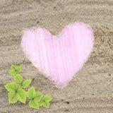 Blocco per grafici dentellare di figura del cuore nella struttura della spiaggia della sabbia Fotografia Stock Libera da Diritti