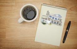 Block av papper med den husteckningen, pennan och kaffe Arkivbild