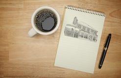 Block av papper med den husteckningen, pennan och kaffe Arkivbilder