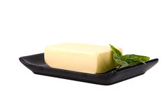 Block of butter and mint leaf on plate Stock Image