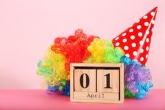 Block calendar and rainbow wig on table. April fool`s day celebration Stock Photos