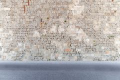 Block cement wall with road in foreground dirty asphalt ahead. Natural castle texture Stock Photography