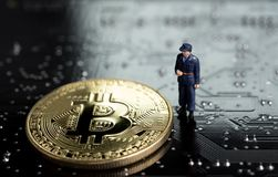 Block chain and Bitcoin safety or security trust concept, miniature figure security guard standing with gold bitcoin on computer. Technology look circuit board stock image