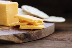 Block of Cheddar Cheese with Slices. Block of cheddar cheese and slices over a rustic background.. Extreme shallow depth of field with selective focus on cheese stock photography