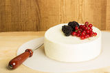 Block of cheese with berries and a knife Stock Photo