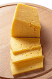 Block of cheese cut into slices. Or portions on a wooden cheeseboard ready to be served as an appetizer or snack, or used as a cooking ingredient Stock Images