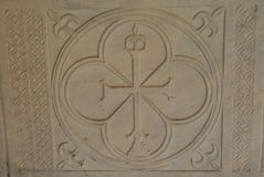 Block of decoratively chiseled sandstone. Aerial view of a block of sandstone chiseled with cross-hatched patterns, fleur de lis, and a cross set in a circle Royalty Free Stock Photos