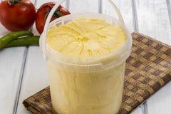 Block der frischen organischen Butter auf einem hölzernen Brett Lizenzfreie Stockbilder