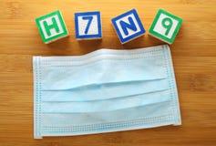 Block des Alphabetes H7N9 mit Gesichtsmaske Stockfoto