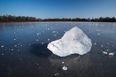 Block des Eises liegend auf der Oberfläche von einem gefrorenen Teich Stockfotos