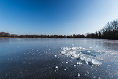 Block des Eises liegend auf der Oberfläche von einem gefrorenen Teich Stockfoto