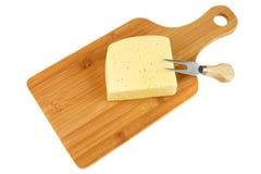 Block des Käses auf Schneidebrett mit einem Messer, lokalisiert auf weißem Hintergrund Lizenzfreie Stockbilder
