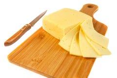 Block des Käses und der Scheiben auf Schneidebrett mit einem Messer, lokalisiert auf weißem Hintergrund Stockfotos